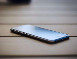 un smartphone posé sur du bois