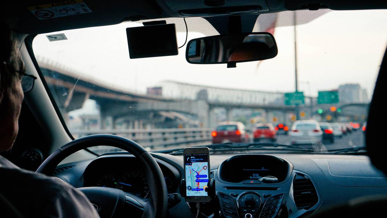 Un chauffeur Uber au volant de sa voiture.