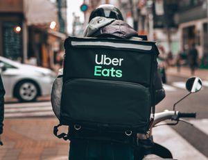 Un livreur Uber Eats de dos dans la rue.