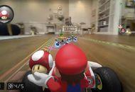Le personnage Mario est dans un karting, tient un champignon dans la main et parcourt un circuit dans un salon.