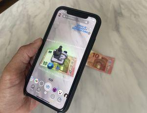 Une personne avec un iPhone X essayant la nouvelle Lense de Snapchat en réalité augmentée