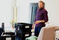 Un homme se tenant au milieu de son salon, en plein déménagement
