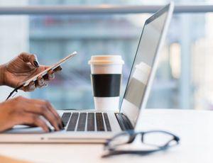 une personne sur son mobile devant son ordinateur