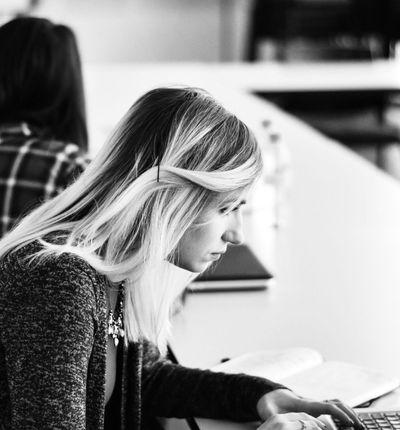 une femme devant son ordinateur en salle de réunion