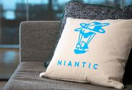 Un coussin arborant le logo de Niantic posé sur un canapé.
