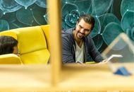 Une personne assise dans un canapé jaune, discutant avec un collègue de bureau