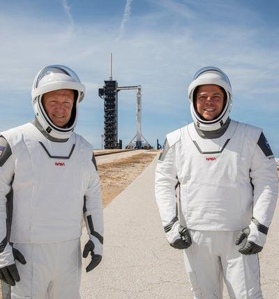 Les astronautes Doug Hurley et Bob Behnken se tiennent devant le site de lancement dans une combinaison spatiale signée SpaceX.