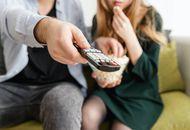 Un couple tient une télécommande et mange du popcorn.