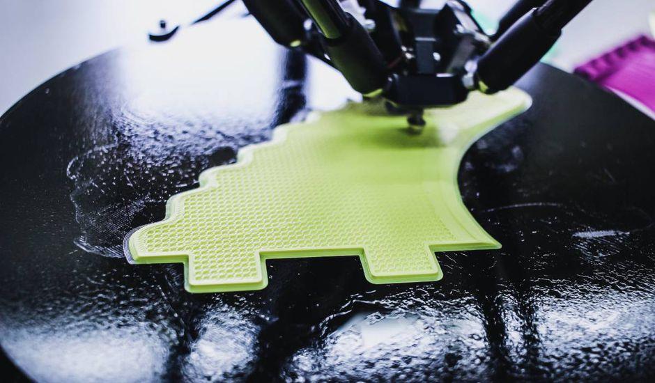 Une imprimante 3D est en train d'imprimer une structure jaune.