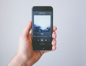 Une personne tient un smartphone dans la main avec l'application Spotify en fonctionnement.