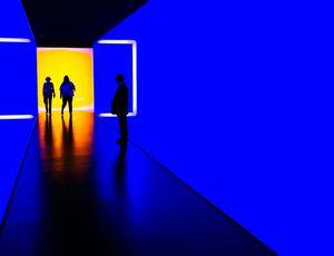 deux personnes entrants dans une galerie sombre