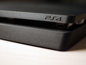 Une PS4 posée sur une table.