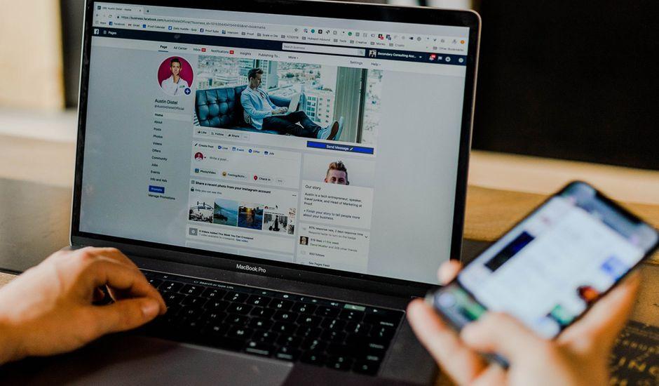 Un homme navigue sur Facebook depuis son ordinateur et tient son smartphone dans la main.