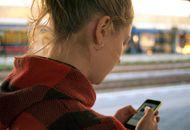Une jeune femme utilise une application de messagerie instantanée sur son smartphone.