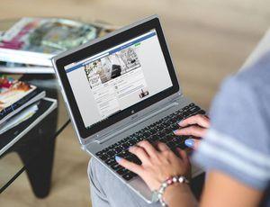 Une femme avec un ordinateur portable ouvert sur le réseau social Facebook.