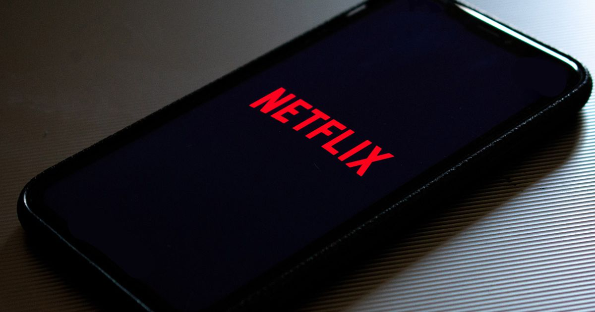 Un smartphone posé sur une table qui lance l'application Netflix