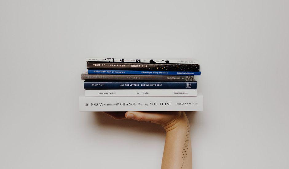 Une femme tient une pile de livres dans la main.